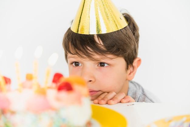 Durchdachter junge, der seinen geburtstagskuchen party betrachtet