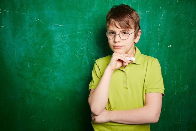 Durchdachter junge mit brille und kreide