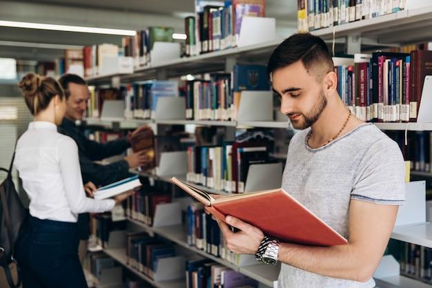 Durchdachter junge sieht wie ein student aus, der mit buch in der bibliothek einer universität steht