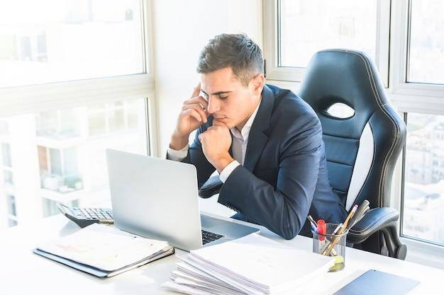 Durchdachter junger geschäftsmann, der laptop auf arbeitsplatz betrachtet