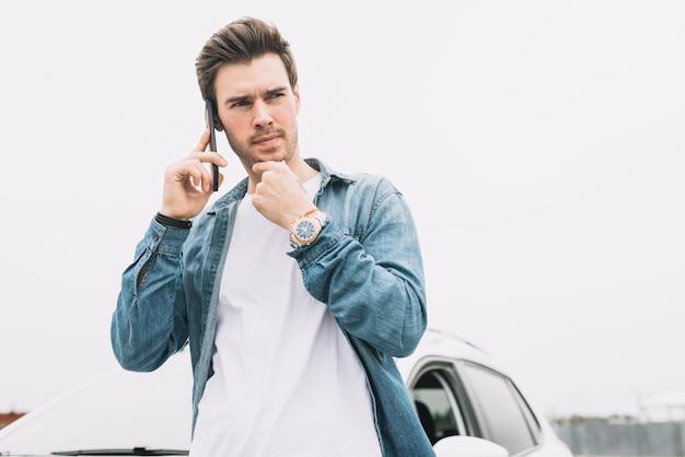 Durchdachter junger mann, der auf dem mobiltelefon steht nahe dem fenster spricht