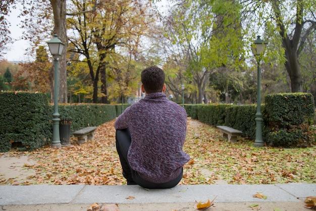 Durchdachter junger mann, der auf treppe im herbstpark sitzt und weg schaut.