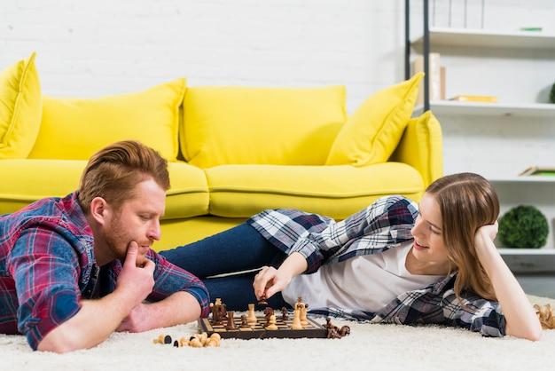 Durchdachter junger mann, der die lächelnde frau spielt das schachspiel betrachtet