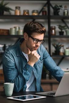 Durchdachter junger mann, der digitale tablette auf küchenarbeitsplatte betrachtet