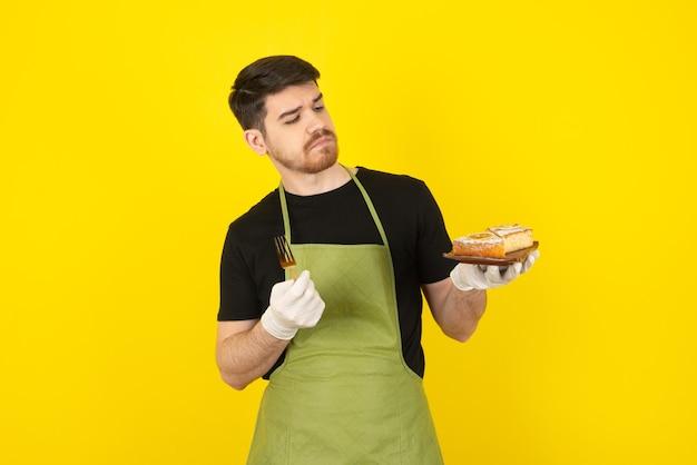 Durchdachter junger mann, der kuchenscheibe auf einem gelb betrachtet.