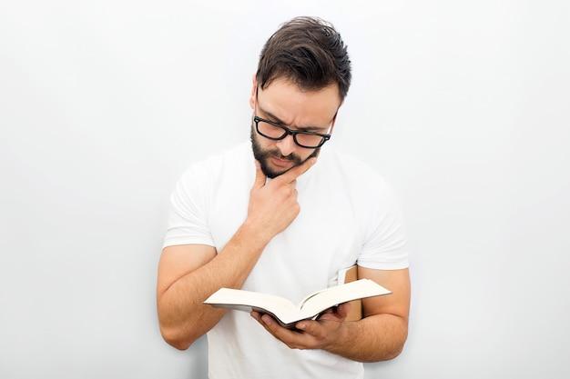 Durchdachter junger mann in den gläsern, die buch stehen und lesen. er hält es in der linken hand. noch einer unter dem kinn.