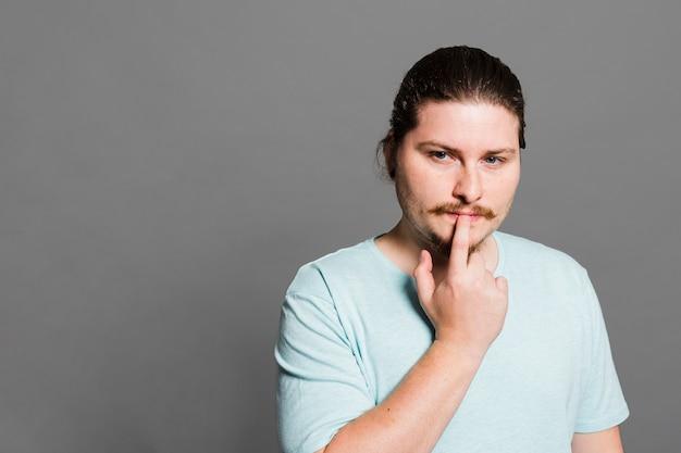 Durchdachter junger mann mit seiner hand auf lippen gegen grauen hintergrund