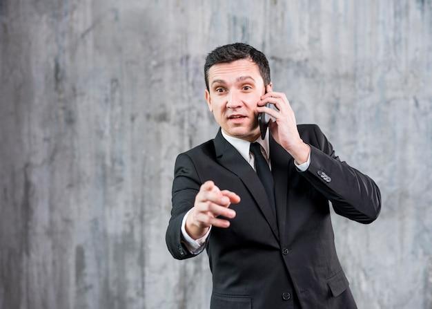 Durchdachter junger stilvoller geschäftsmann, der am telefon spricht