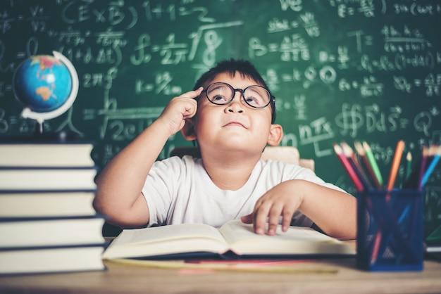 Durchdachter kleiner junge mit buch im klassenzimmer
