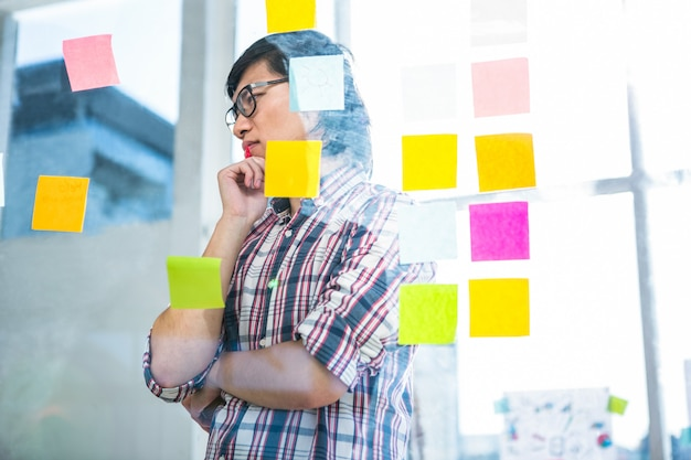 Durchdachter kreativer geschäftsmann, der klebrige anmerkungen im büro betrachtet