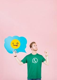 Durchdachter mann, der aufwärts beim anhalten des blinzelns der emoji spracheblase zeigt