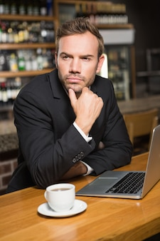 Durchdachter mann, der laptop verwendet und einen kaffee trinkt