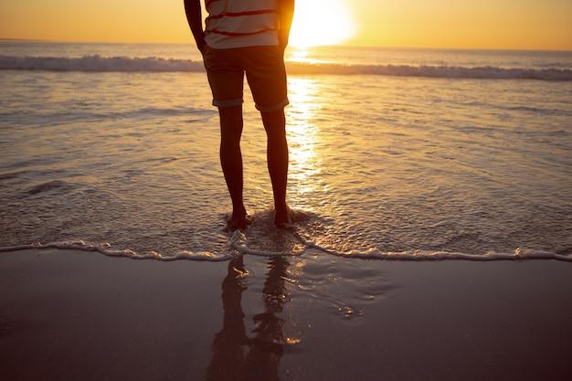 Durchdachter mann, der mit den händen in der tasche auf dem strand steht