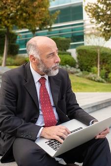 Durchdachter reifer geschäftsmann unter verwendung des laptops