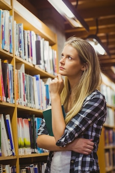 Durchdachter student, der bücherregal in der bibliothek betrachtet