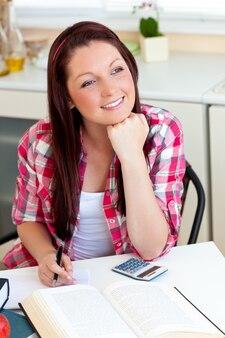 Durchdachter student, der zu hause ihre hausarbeit tut