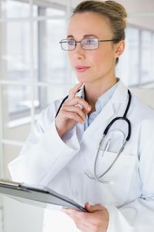 Durchdachter weiblicher doktor mit klemmbrett im krankenhaus