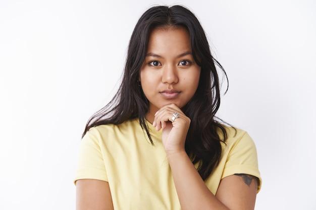 Durchdachtes attraktives junges malaysisches mädchen mit gesichtsnarben und akne, das das kinn berührt und entschlossen in die kamera schaut und denkt, verträumt vor weißem hintergrund in gelbem t-shirt zu stehen