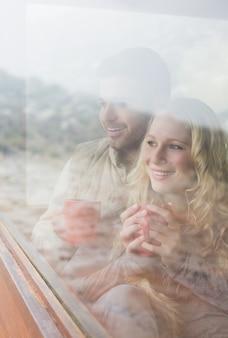 Durchdachtes glückliches paar mit den kaffeetassen, die durch fenster schauen