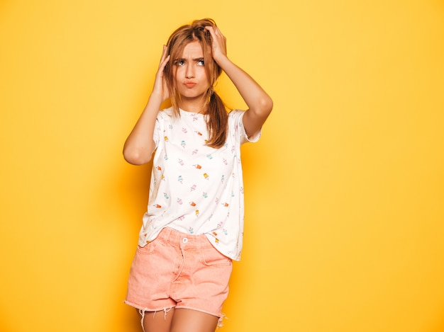 Durchdachtes mädchen des jungen schönen hippies in der modischen sommerjeans-kurzen hosen kleidet. sexy sorglose frau, die nahe gelber wand aufwirft beiseite schauen
