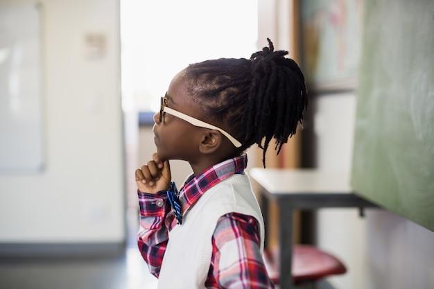 Durchdachtes schulmädchen, das mit der hand auf kinn im klassenzimmer steht