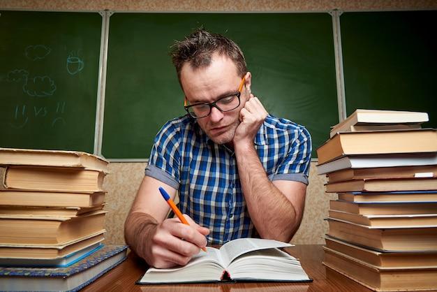 Durcheinandergebrachter junger mann in den gläsern ein buch lesend.