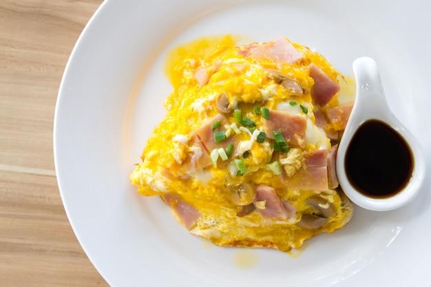 Durcheinandergemischte omlette eier mit schweinefleischschinken auf reis.