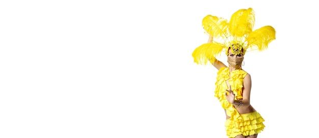 Durchführen. schöne junge frau im karnevals-maskeradenkostüm mit gelben federn, die auf weißem hintergrund tanzen. konzept der feiertagsfeier, der festlichen zeit, des tanzes, der partei, des glücks. copyspace