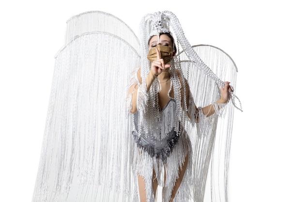 Durchführen. schöne junge frau im karnevals-maskeradenkostüm mit weißen federn, die auf weißem hintergrund tanzen. konzept der feiertagsfeier, der festlichen zeit, des tanzes, der partei, des glücks. copyspace