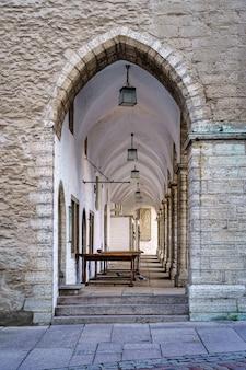 Durchgang unter einem mittelalterlichen gebäude mit bögen und steinmauern. tallinn estland.