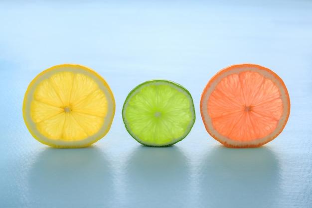 Durchscheinende scheiben zitronenorangen-grapefruit und limette auf blau.