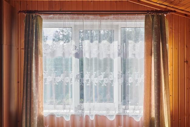 Durchscheinender weißer vorhang im alten stil am fenster im zimmer der hütte. fenster ist mit einem transparenten vorhang bedeckt. sonniges morgenlicht im hauszimmer.