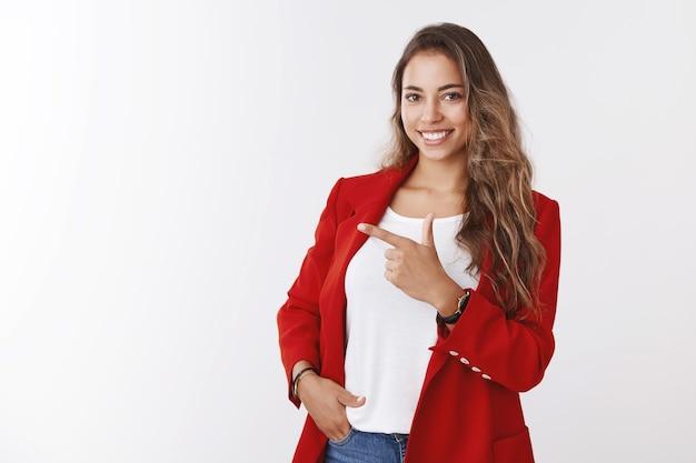 Durchsetzungsfähige, gut aussehende unternehmerin, die selbstbewusste pose posiert, zeigt mit dem zeigefinger beiseite und zeigt kopienraum selbstbewusste, geschickte geschäftsfrau mit interessanter werbung