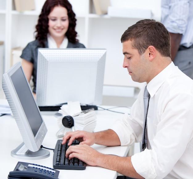 Durchsetzungsfähige junge geschäftsleute, die an den computern arbeiten