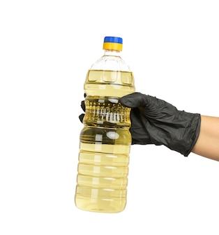 Durchsichtige plastikflasche mit sonnenblumenöl in der hand, nahaufnahme