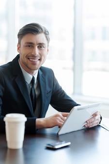 Durchsucht seinen posteingang. ein gutaussehender geschäftsmann, der sein tablet benutzt, während er sitzt und eine pause macht