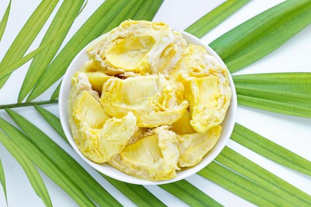 Durian in der weißen platte auf tropischer palmblattoberfläche