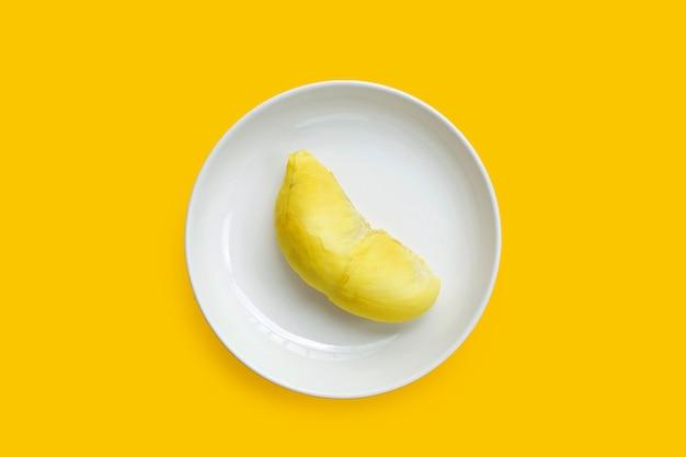 Durian in weißer platte auf gelbem hintergrund.
