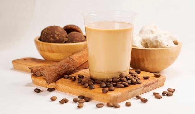 Durian-kaffee im plastikbecher bestreut mit kaffeebohnen, zimt und palmzucker