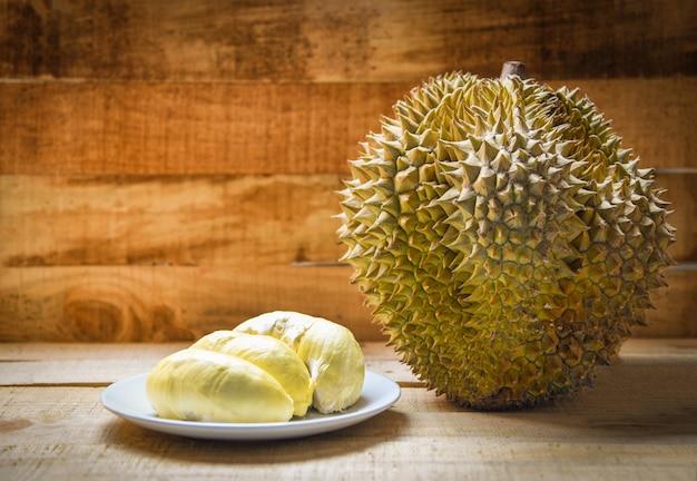 Durian riss auf platte und durianfrucht auf hölzernem hintergrund auf sommer