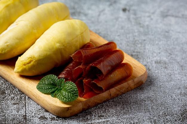 Durian und snacks auf der dunklen oberfläche.