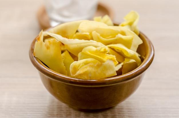 Durianchips brieten snackfrucht im braunen schlag auf hölzernem hintergrund
