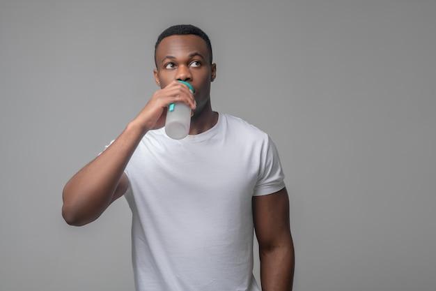 Durst, wasser. junger dunkelhäutiger mann in weißem t-shirt trinkwasser aus sportflasche mit blick auf die seite auf hellem hintergrund