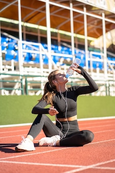 Durstige junge fit frau trinkwasser aus plastikflasche
