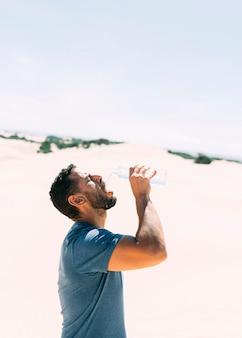 Durstiger afrikanischer mann, der wasser in der wüste trinkt, um durst und hitzewelle zu beruhigen
