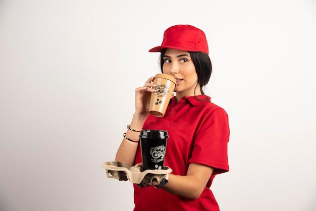 Durstiger kurier, der eine tasse kaffee trinkt. hochwertiges foto
