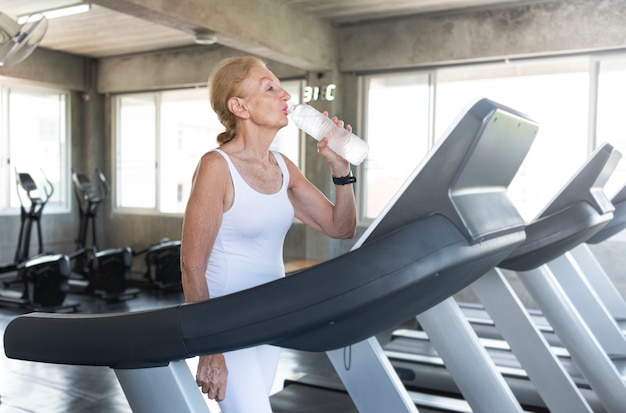 Durstiges trinkwasser und übung der älteren frau, die an der turnhalleneignung rüttelt. älterer gesunder lebensstil.