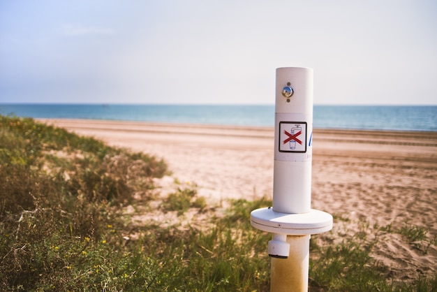 Duschen, um den sand von den füßen der am strand befindlichen badegäste mit warnzeichen von queno zu entfernen, ist ein trinkwasser.