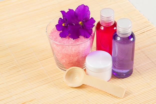 Duschgel, badesalz und körperfeuchtigkeitscreme mit löffel auf einer bambusmatte