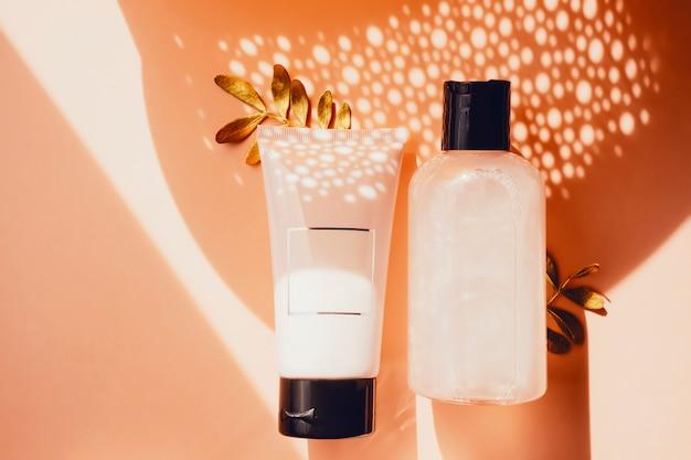 Duschgel, handcreme und bodylotion mit goldenem blattdekor. moderne konzeptebenenlage der umweltfreundlichen hautpflege der schönheit. flaschen. umweltfreundliches konzept